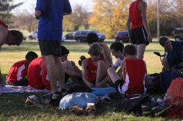 The cross country meet relax before the beginning of the boys meet.