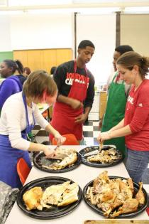Ms. Laura Spiegelhalter (Foods) helps students carve the main dish. Photo by Alexis Weaver