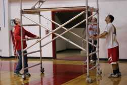 Graham Manuel and Tyler Johnson, (12) move the ladder across the gym to get to another banner.