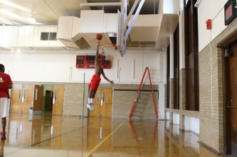 Miles Thompson (12) practices his dunking skills before practice making sure his is warmed up and ready.