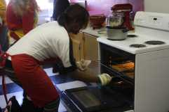 Jasmyn Hamilton (12) takes the food out of the oven. Photo by Destony Curry.