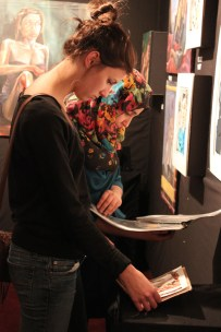 Maha Jabbar (12) and another student browse their fellow Va student's artwork.