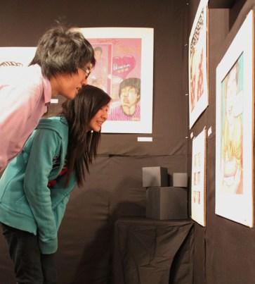 Bowen Sung (12) and a visitor examine a drawing he created.