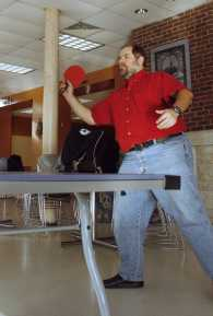 Mr. Smith plays ping pong with the kids and serves the ball to his opponent.