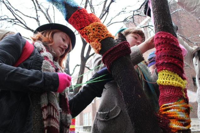 Clare Hagan (11) and Irene Mudd (12) attach smaller yarn blocks to a tree's branches. Photo by Kelsi White.