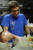 """""""I like tossing salad,"""" said Alex Rubino(11) as he used his gloved hands to mix the assorted vegetables. Photo by Jack Steele Mattingly"""