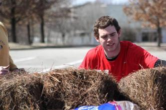 Andrew Olson (12) loads pine straw onto the back of a truck.