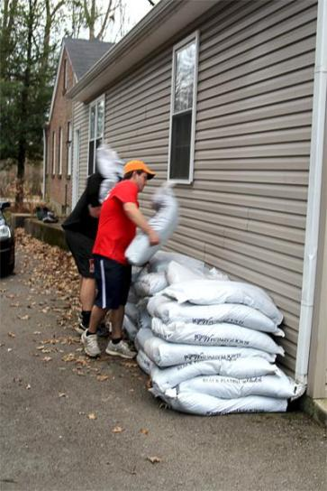 Mclean Long (12) helps stack 40 bags of mulch next to a house.