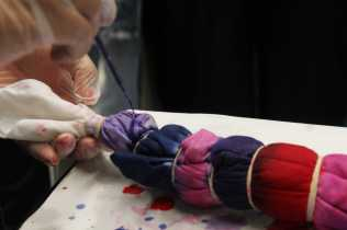 Student adds final colors to tie-dye t-shirt.