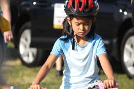 Little girl gets ready to ride her bike to the start line