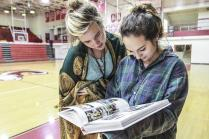 Senior Katie DeAngelis and junior Jenna Farineau glance at baby ads as soon as DeAngelis picked up her yearbook during white 4. Photo by Yazmin Martinez