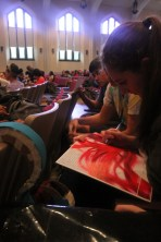 Students sign yearbooks as they wait to hear principal candidates speak. Photo by Allison Traylor