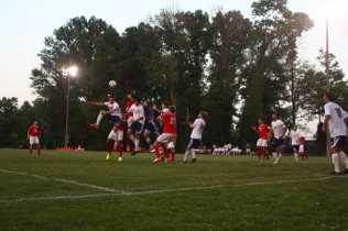 Players jump to head the ball from a goal kick by Manual's Andrew Hagan (10, #1)