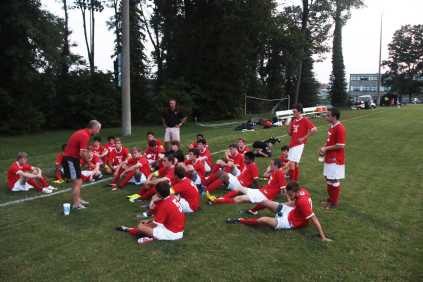 Manual varsity soccer team sits listening to the coach during halftime.