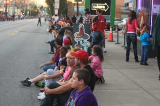 Row of kids sit patiently on Bardstown road in a lot of anticipation