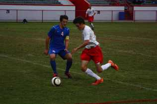 Riley Hook (10, #25) dribbles the ball down the side of the field next to a close-following CAL player