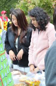 WISE members Emily Zeng (12) and Natasha Mundkur (11) sell baked goods at the Carnival.