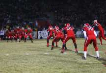 The football team lines up as they wait for Chris Roussell (10, #46) to kick the football towards the goal.