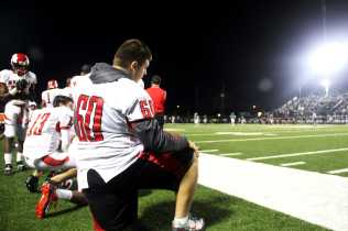 #60 as well as fellow Manual football players kneel as the game comes to a close.