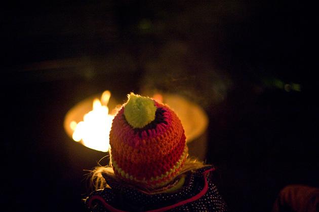 Kleines Mädchen mit Mütze sitzt vor dem Feuer