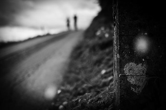 Aufnahme von einem gesprühten Herz auf einer Mauer, im Hintergrund zwei unscharfe Personen auf einem Spazierweg