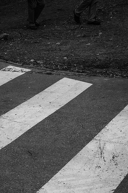 Schwarz-Weiss-Bild von einem Fussgängerstreifen mit Füssen