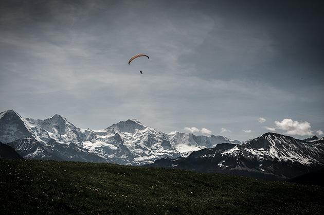 Die Bergkette mit Eiger, Mönch und Jungfrau bei Tageslicht. Im Vordergrund ein einzelner Gleitschirm am Himmel.