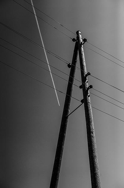 Fotografie eines alten Strommastes – im Hintergrund ein Kondensstreifen eines Flugzeuges am Himmel