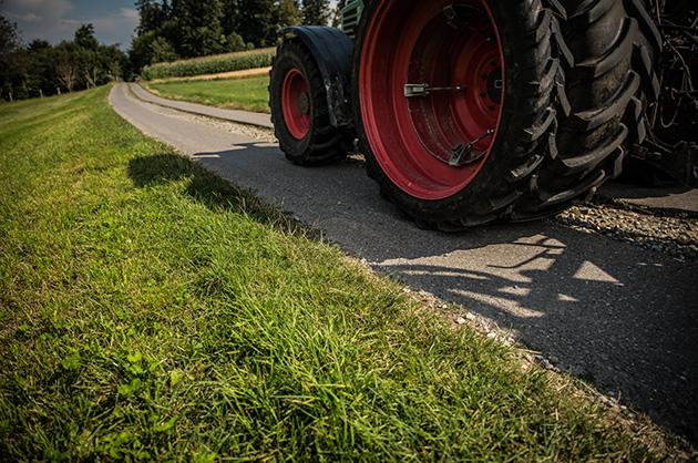 Die Räder eines vorbeifahrenden Traktors auf einer Feldstrasse