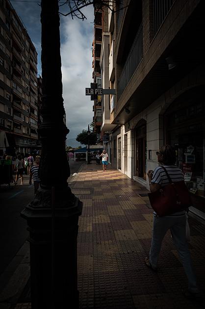 Alter Dorfteil von Cullera, Spanien, Provinz Valencia. Ein Mann läuft auf dem Gehsteig in einem Lichtkegel. Nikon D810, 20mm/1.8