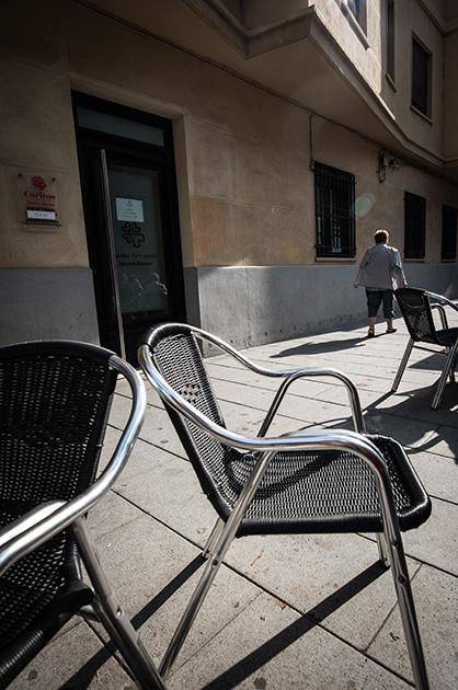 Cullera, Spanien. Eine Frau läuft auf dem Gehstieg, im Vordergrund drei Kneipenstühle aus Metall. Nikon D810, 20mm/1.8