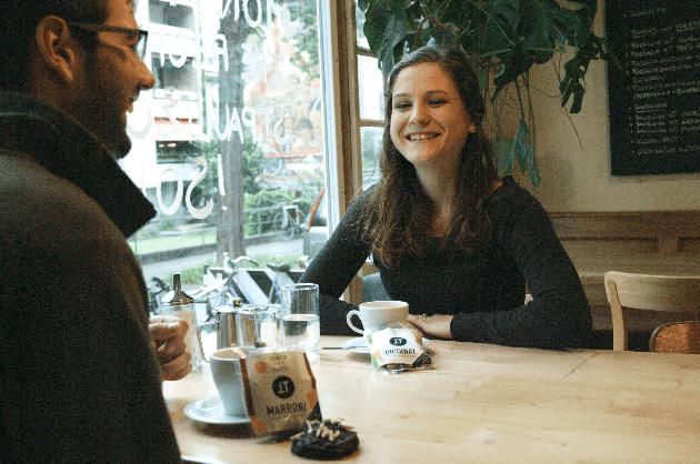 Verpackungsdesign Torta per Tutti – Standbild aus dem Werbefilm. Ein Mann und eine Frau sitzen an einem Holztisch, essen Torta per Tutti und trinken Kaffee