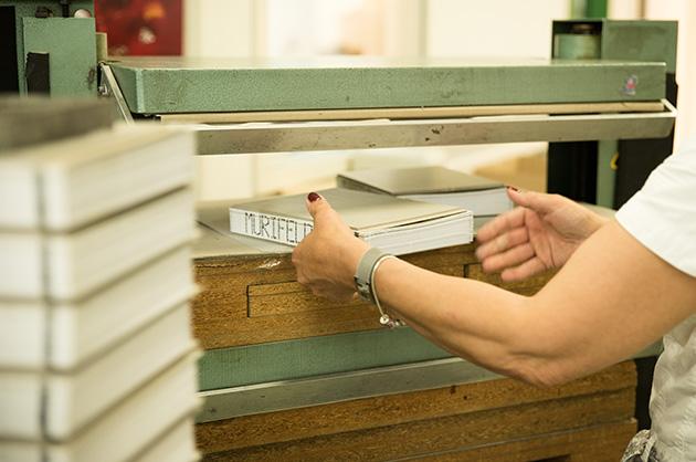Die geklebten Deckel werden mit hohem Druck in einer Presse zusammengepresst