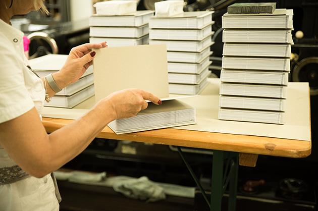 Ein Karton wird zum aufnehmen der Leimfeuchtigkeit vor die Buchblöcke gelegt