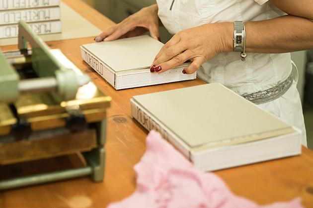 Murifeldbuchproduktion – die Graukartondeckel werden von Hand auf die Buchblöcke geklebt