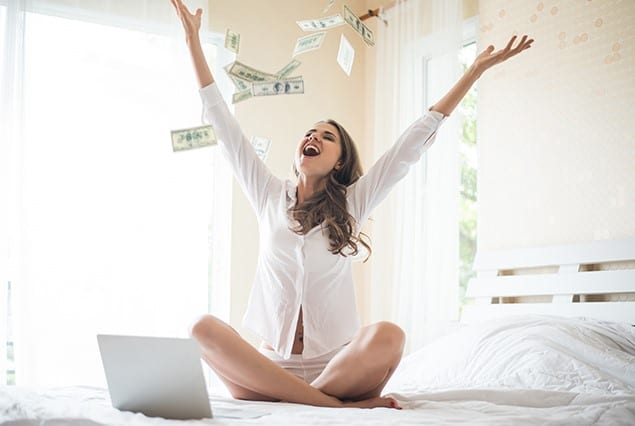 happy woman sitting in a bed with laptop and throwing money