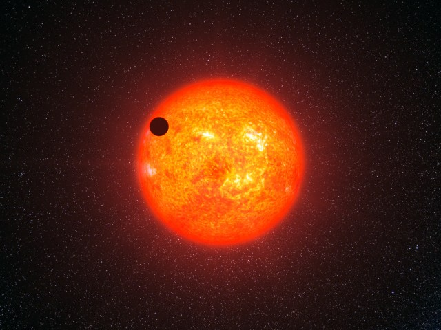 """The planet Gliese 1214b was initially described as a possible """"water world,"""" and the idea caught the public imagination. But subsequent examination, and the characterizing of other super-Earths and sub-Neptunes, has led to a different conclusion: that the planet is most likely covered by a hydrogen/helium envelope and a thick film of sooty dust. (Artist rendering by L. Calçada, European Space Observatory.)"""