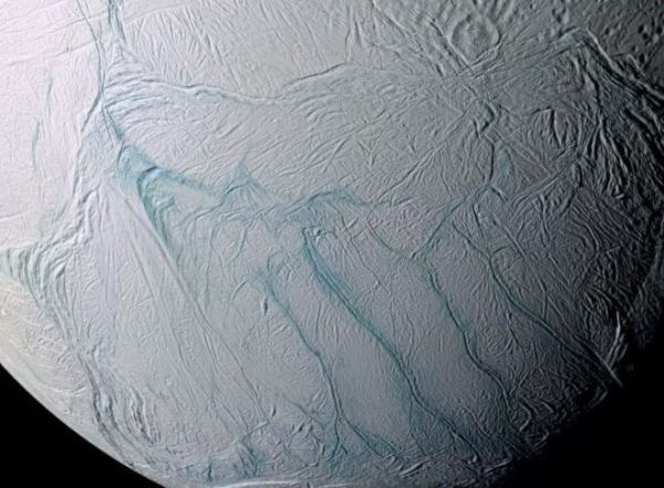 "A view of Enceladus' southern hemisphere in enhanced color (IR-green-UV). The ""tiger stripe"" fractures, the source of plumes venting gas and dust into space, are prominently visible in the center. {NASA/JPL-Caltech/SSI/Lunar and Planetary Institute, Paul Schenk (LPI, Houston)"