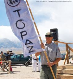 Banners representing all of the American concentration camps during World War II, the Crystal City Internment Camp, and a banner honoring the 100th Battalion/442nd Regimental Combat Team/Military Intelligence Service, are part of each year's Manzanar Pilgrimage. Carrying the Topaz banner is Dave Goto.