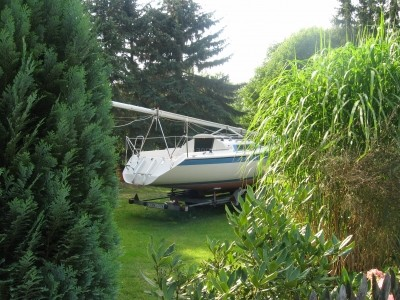 Segelboot mit gelegtem Mast auf einer Wiese in einem Garten. Symbolbild zum Thema Kauf und Eigentum.