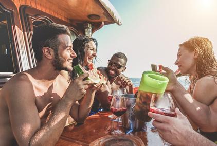 Junge Menschen an Bord eines Bootes, die Sangria trinken.