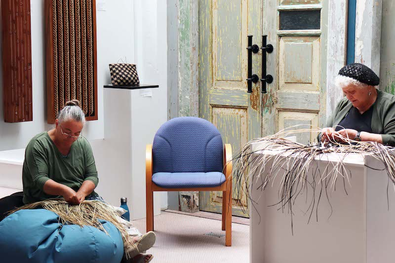 Weavers Pip Devonshire and Sonia Snow sit at their work
