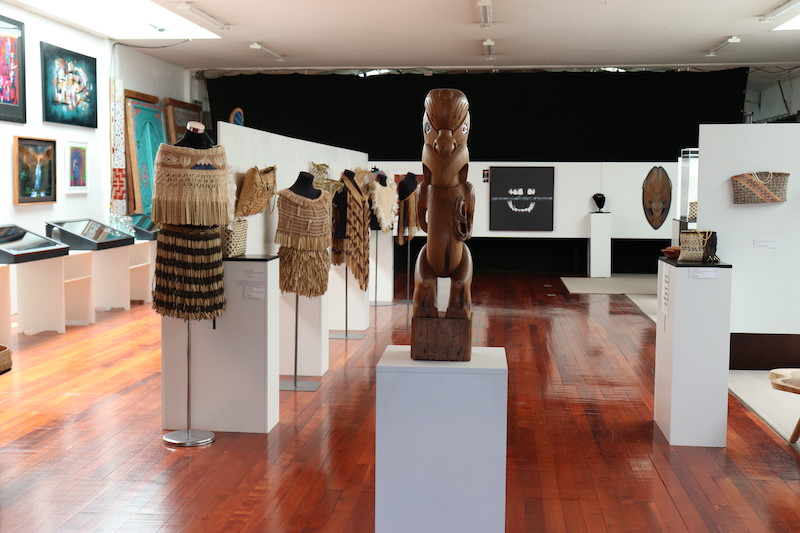 Image shows inside Toi Matarau Gallery - there are a number of woven pieces on display as well as a carved pou.
