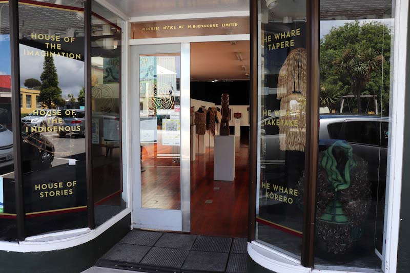 Image shows the entrance to the Māoriland Hub. On each side of the door is gold text - house of the imagination, house of the indigenous, house of stories - he whare tapere, he whare taketake, he whare korero. Inside the doors you can see into an art gallery with Maori artworks on display