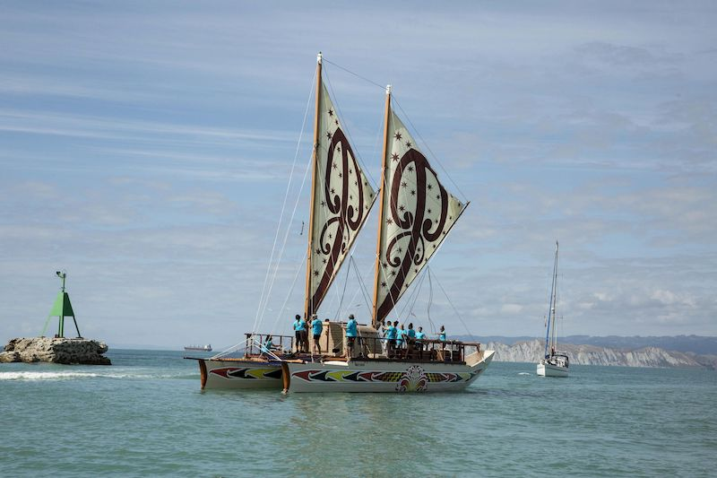 Image shows a double hulled waka with beautiful Māori designs on the water
