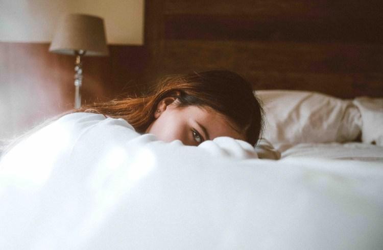 Femme tête posée tranquillement sur un lit.