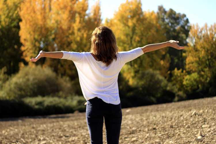 Femme bras écartés de dos qui respire largement