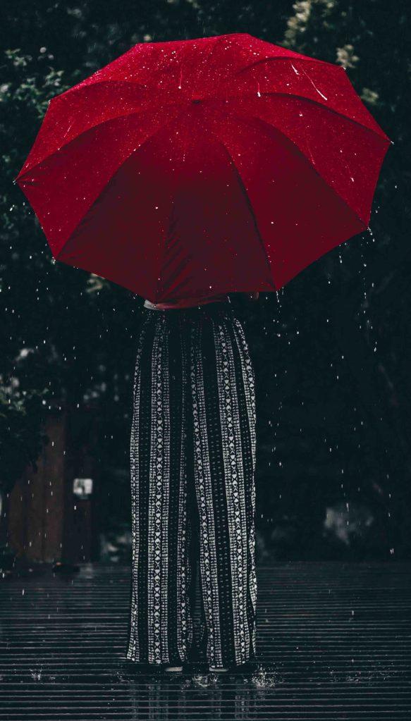 Femme derrière un grand parapluie rouge