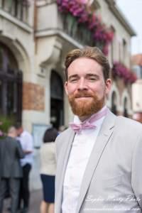 portrait de marié en costume beige et noeud papillon rose