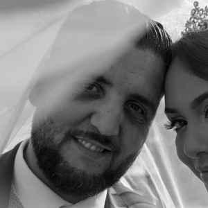 portrait de mariés en noir et blanc sous le voile de la mariée avec son diadème